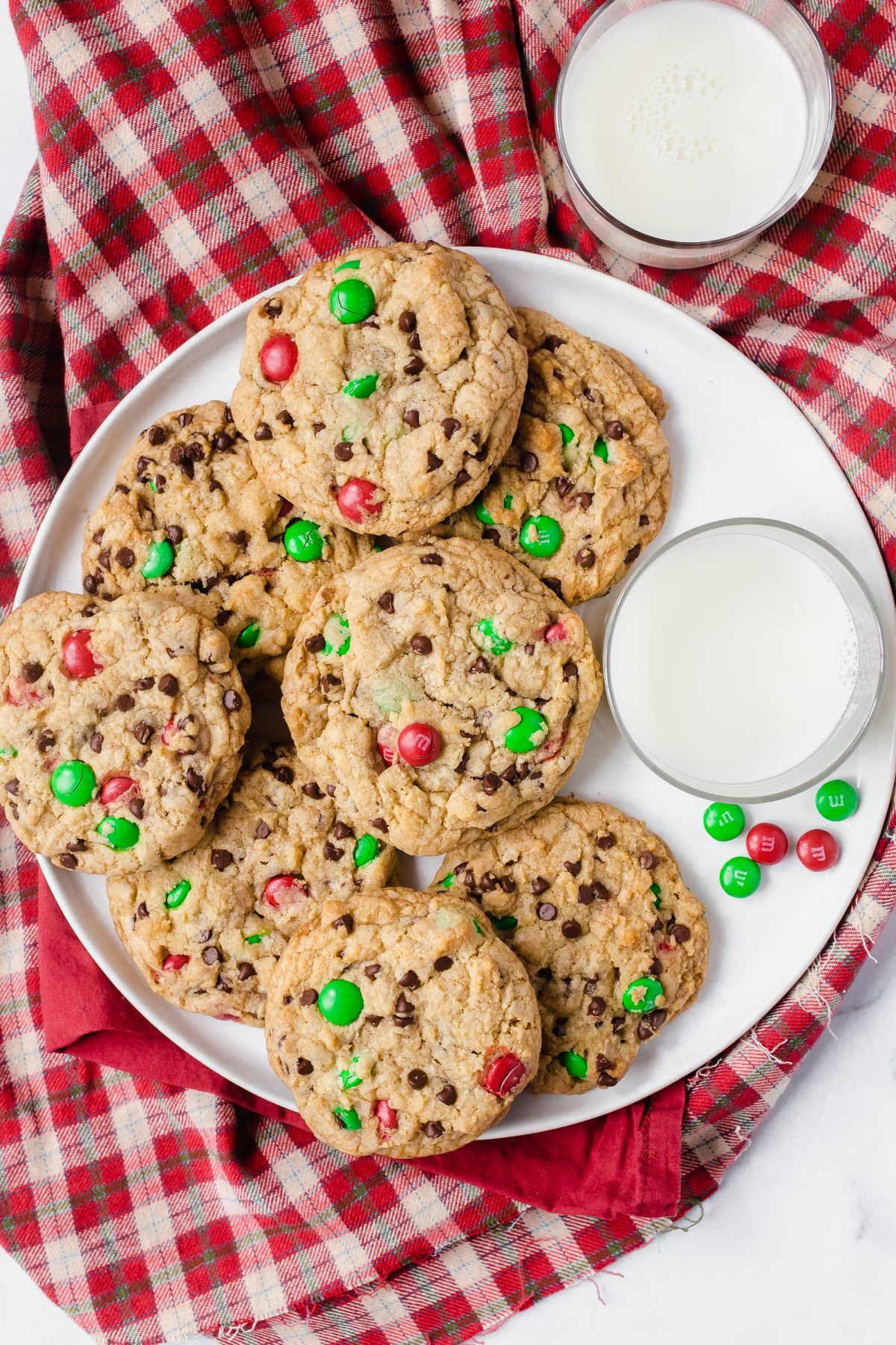 A white plate of large red and green M&M cookies with 2 glasses of milk