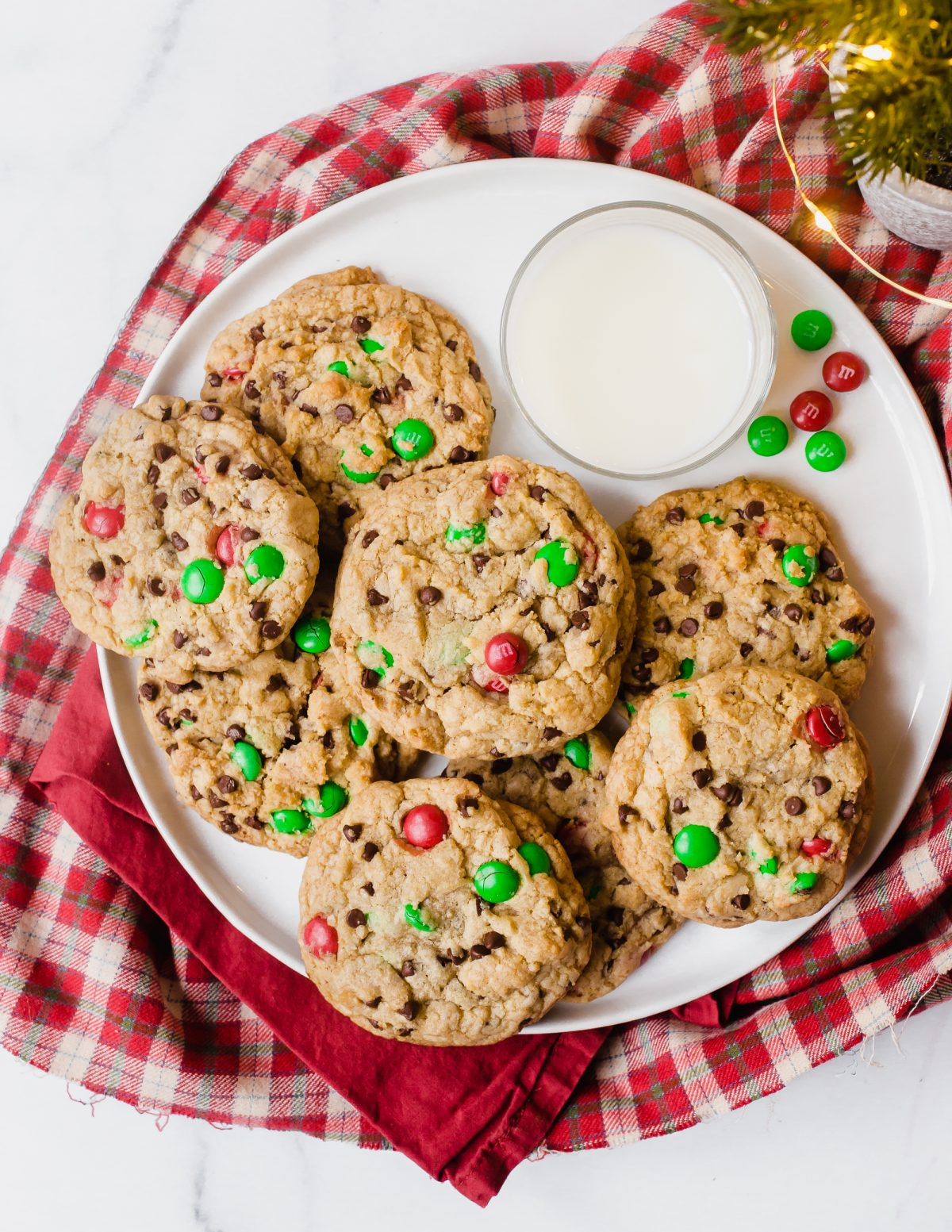 Overhead shot of a plate of Chocolate Chip M&M Christmas cookies with a glass of milk