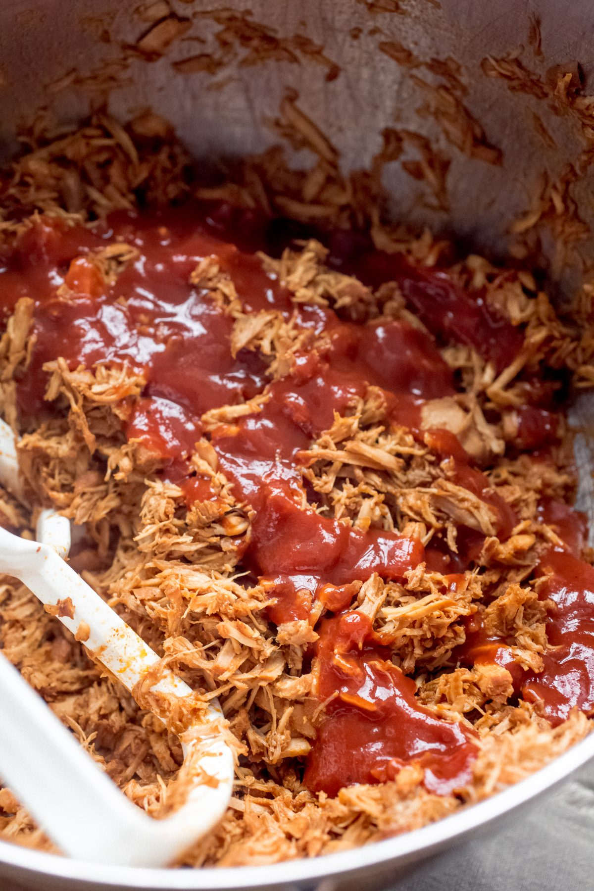A mixing bowl filled with shredded pork shoulder covered in barbecue sauce