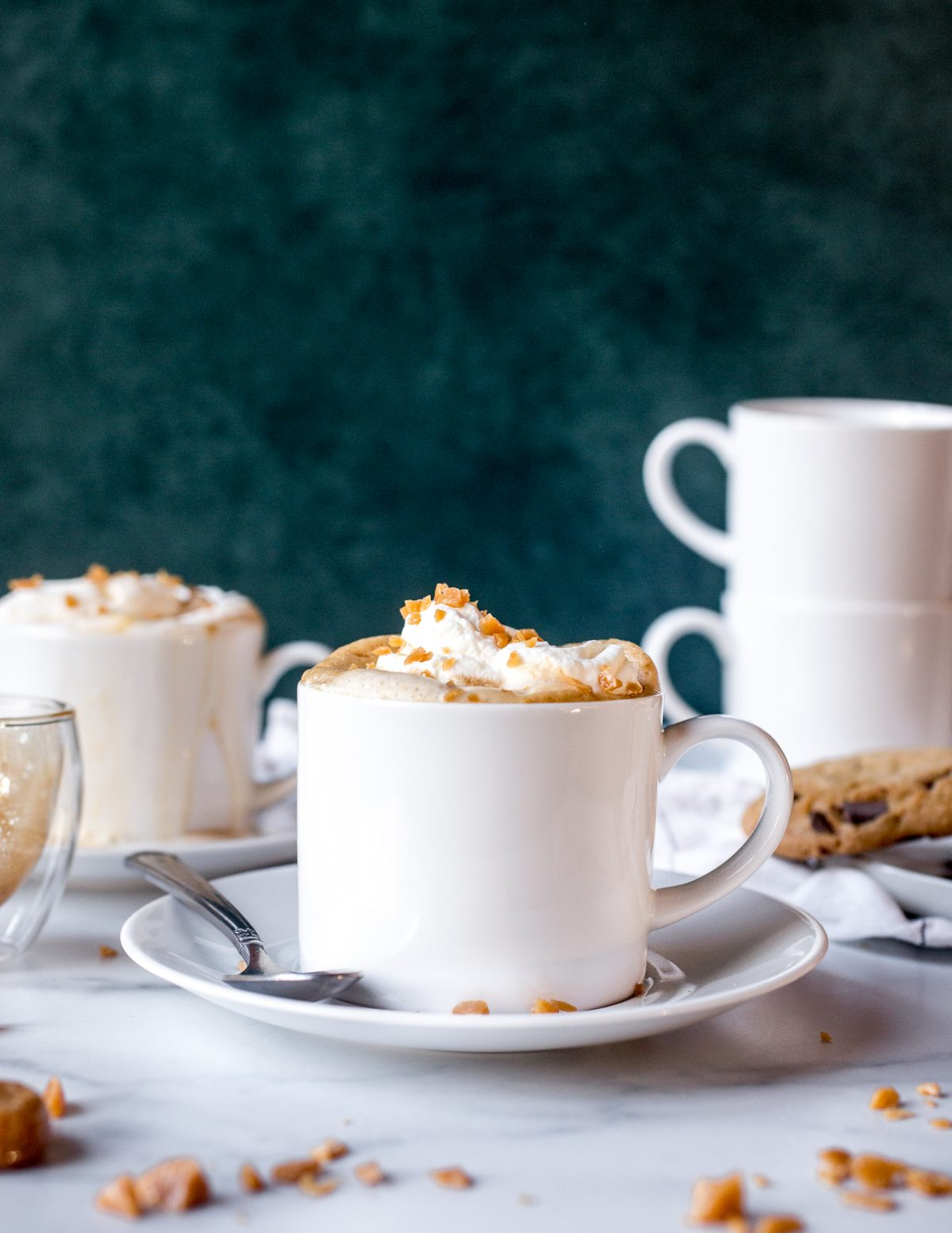 A frothy caramel latte in a white mug on a saucer surrounded by caramel hard candies