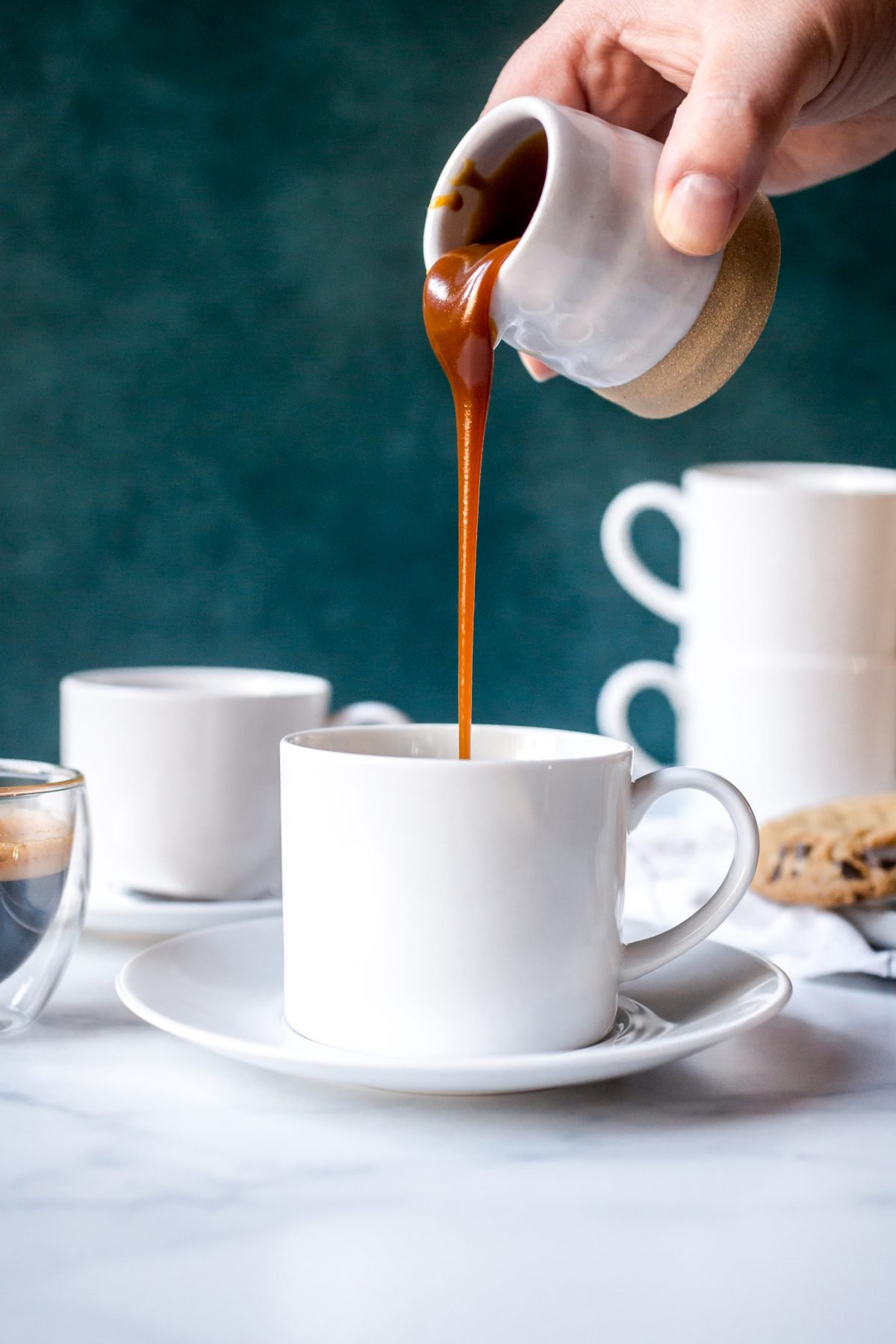 A hand pouring caramel sauce into a white coffee mug on a saucer