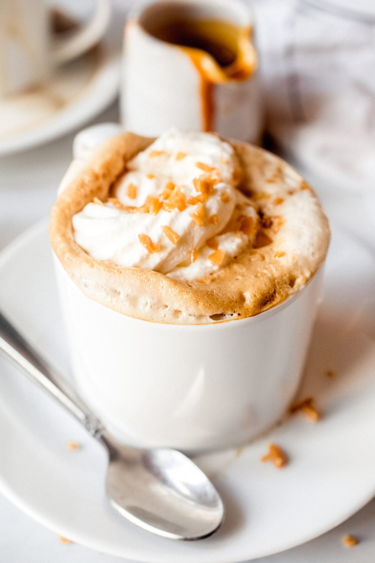 A caramel latte topped with whipped cream and caramel pieces on a white saucer with a spoon