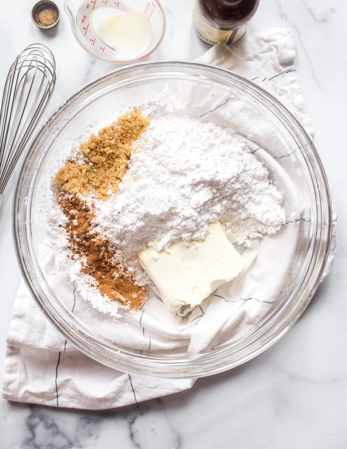 Powdered sugar, cinnamon, and softened cream cheese in a glass mixing bowl