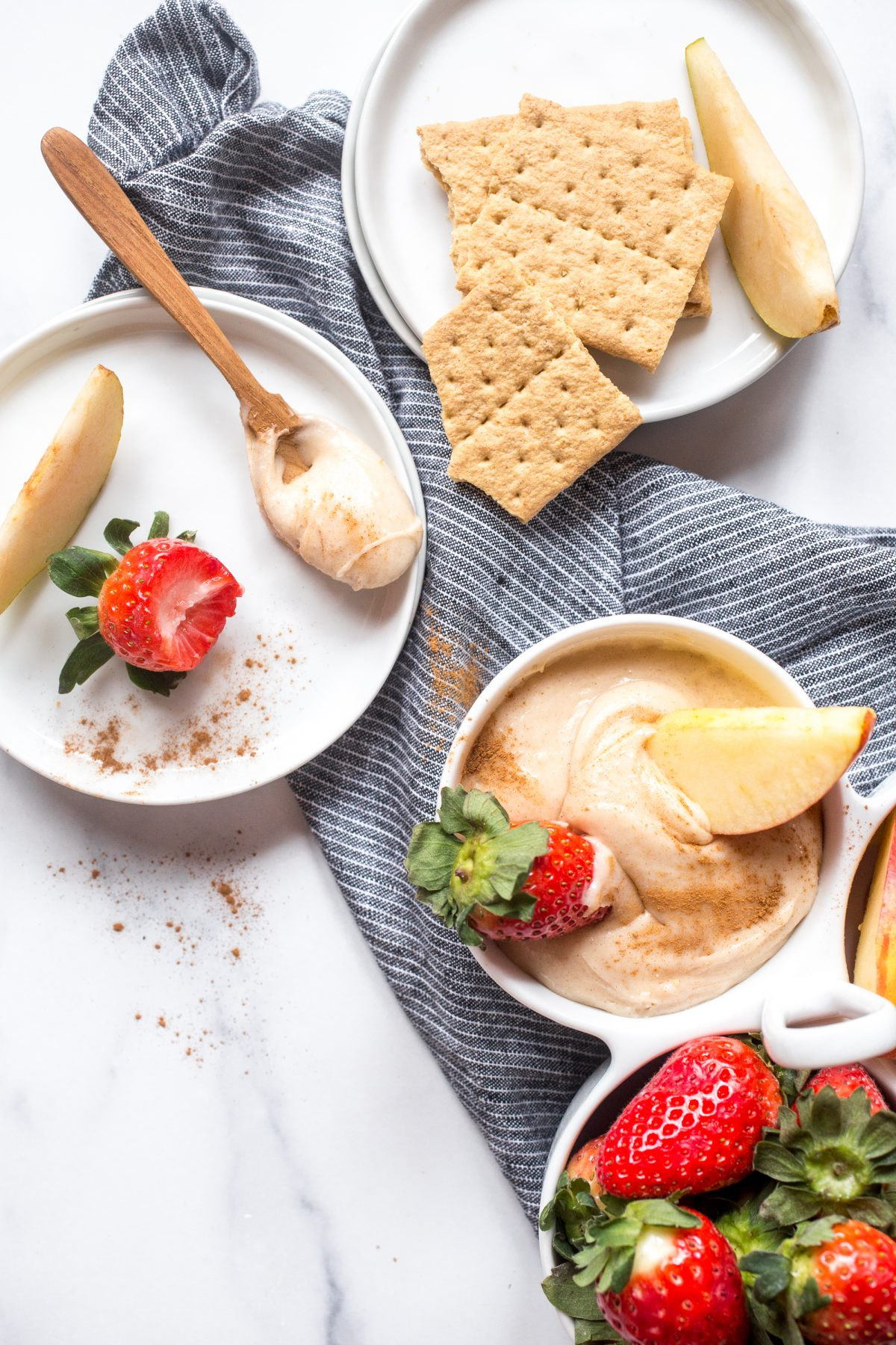 A spoonful of cream cheese dip on a small white plate with a strawberry next to more dip and strawberries