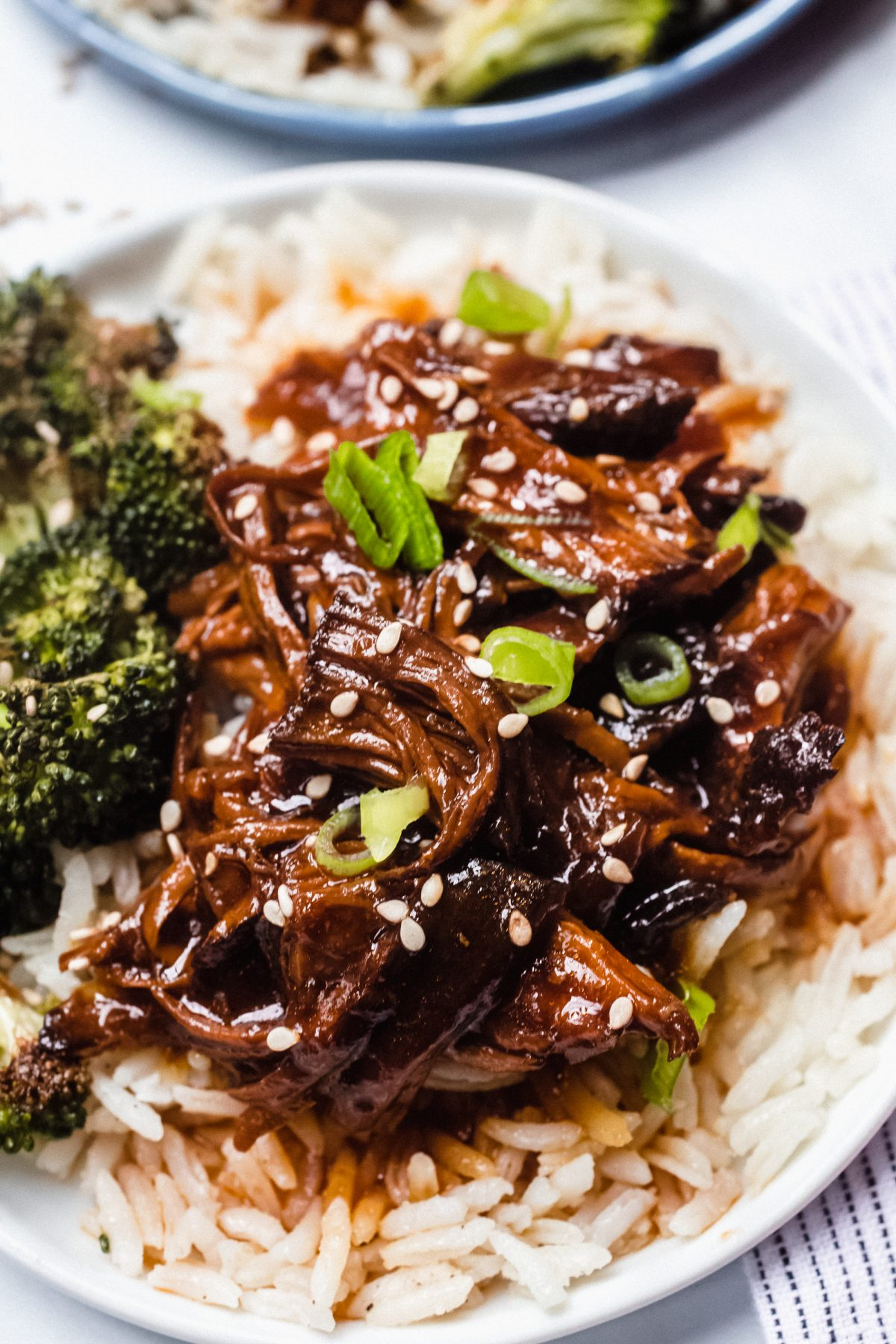 Close up photo of Instant Pot Honey Garlic Chicken served over rice with roasted broccoli on the side.