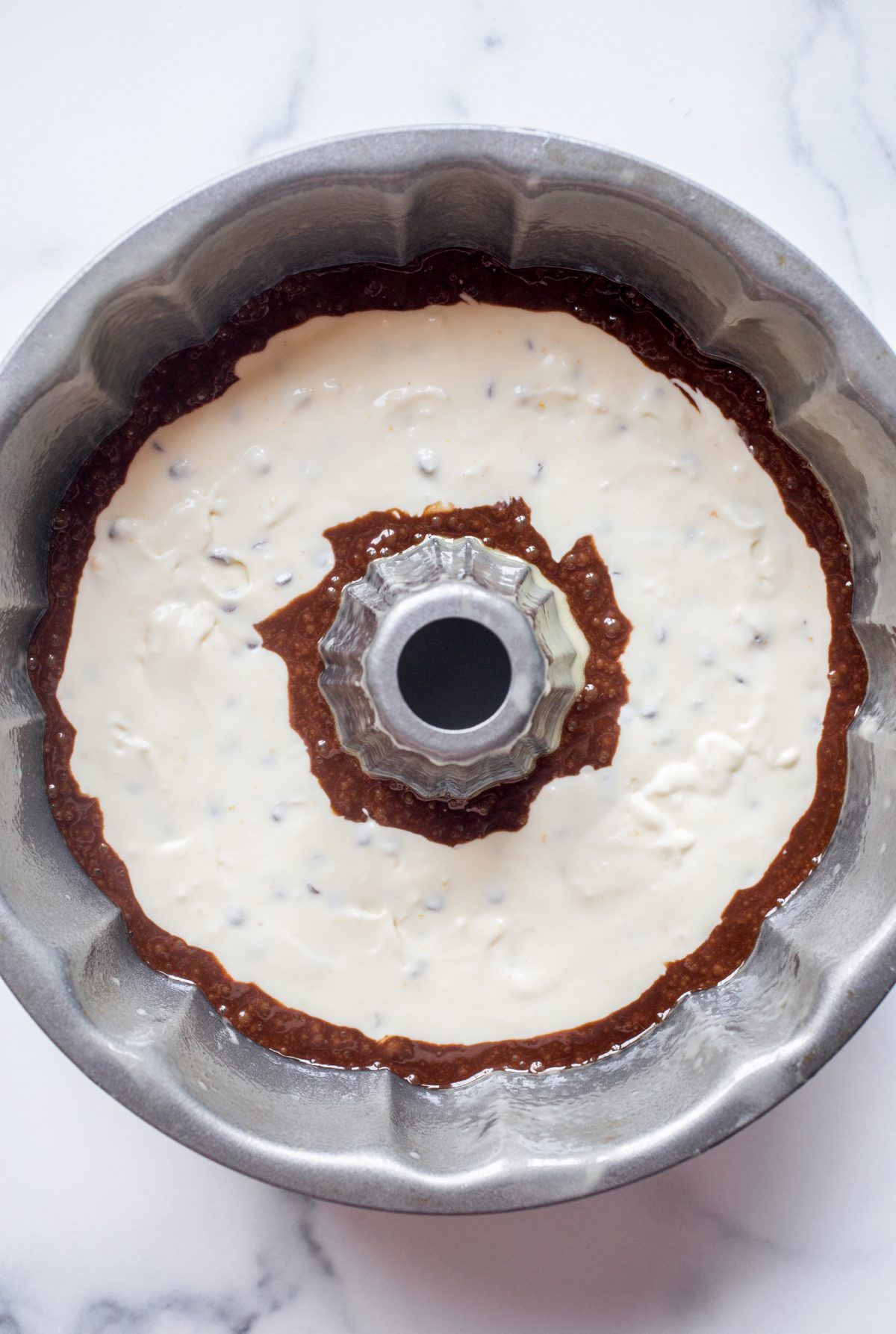 A bundt cake pan with chocolate cake batter under a layer of cannoli cream