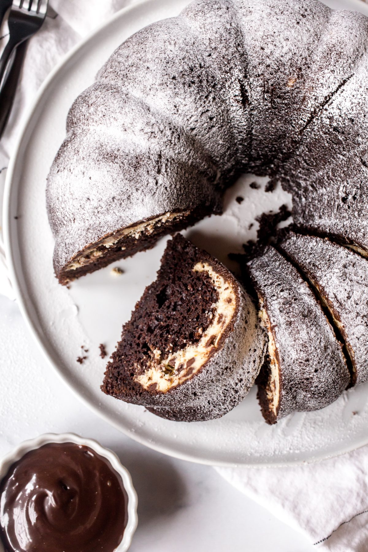 Top shot of a chocolate bundt cake dusted with powdered sugar and filled with cannoli cream