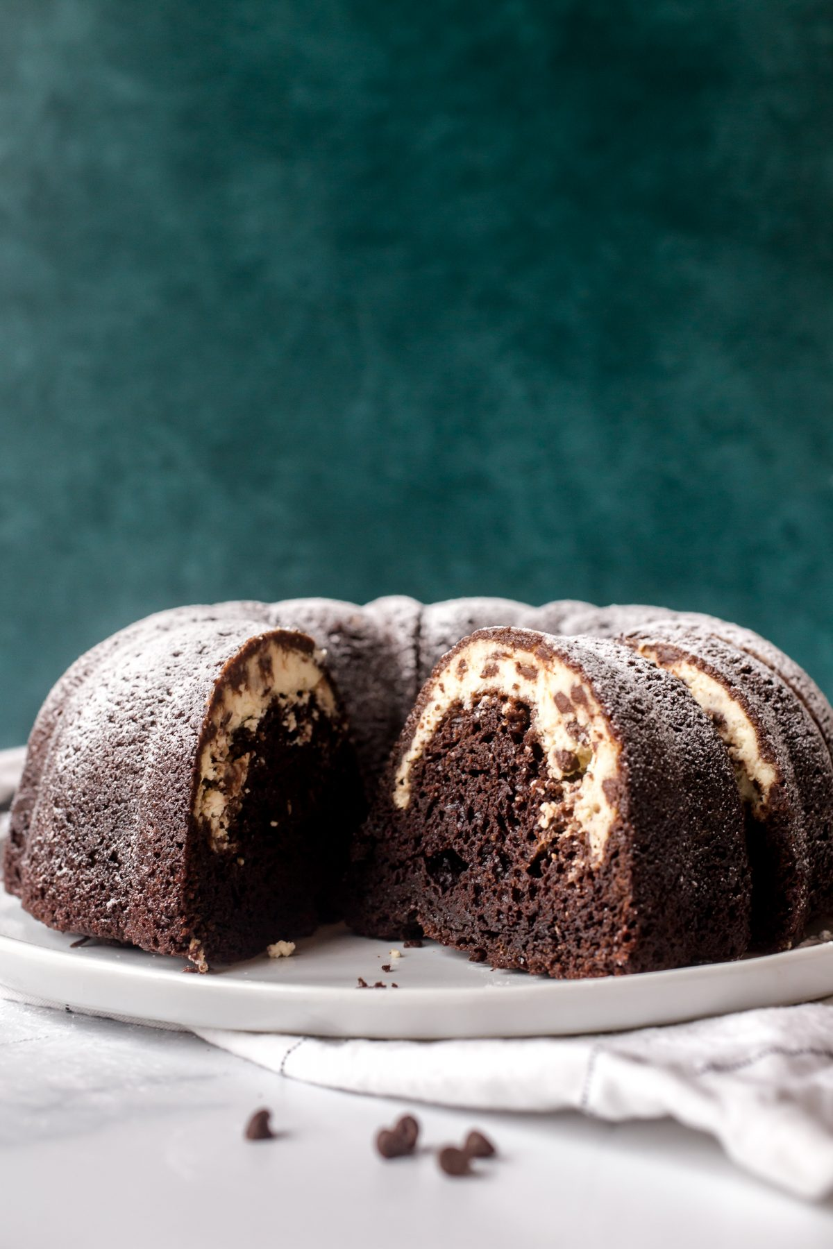 Side view of a chocolate cannoli bundt cake filled with ricotta, cream cheese, and chocolate chips