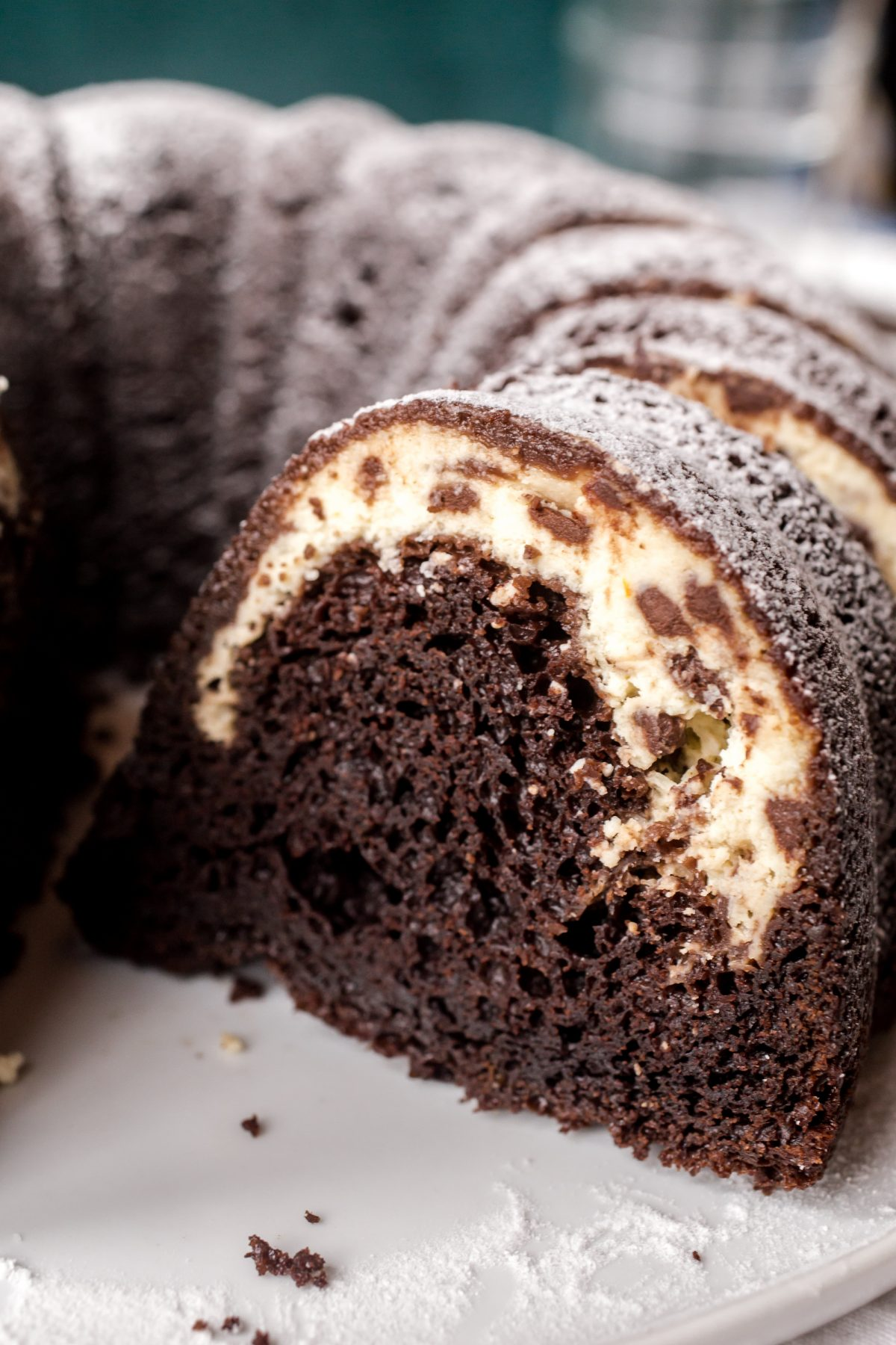 A cross section of a chocolate bundt cake filled with cannoli cream