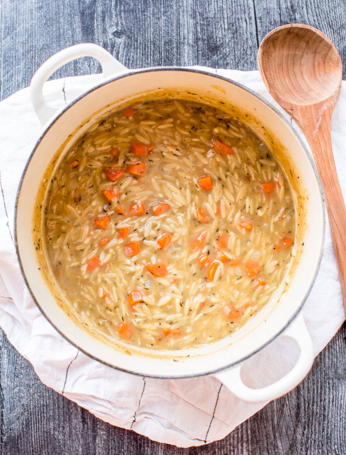 Overhead shot of a creamy chicken orzo soup with carrots in a white Dutch oven next to a wooden spoon