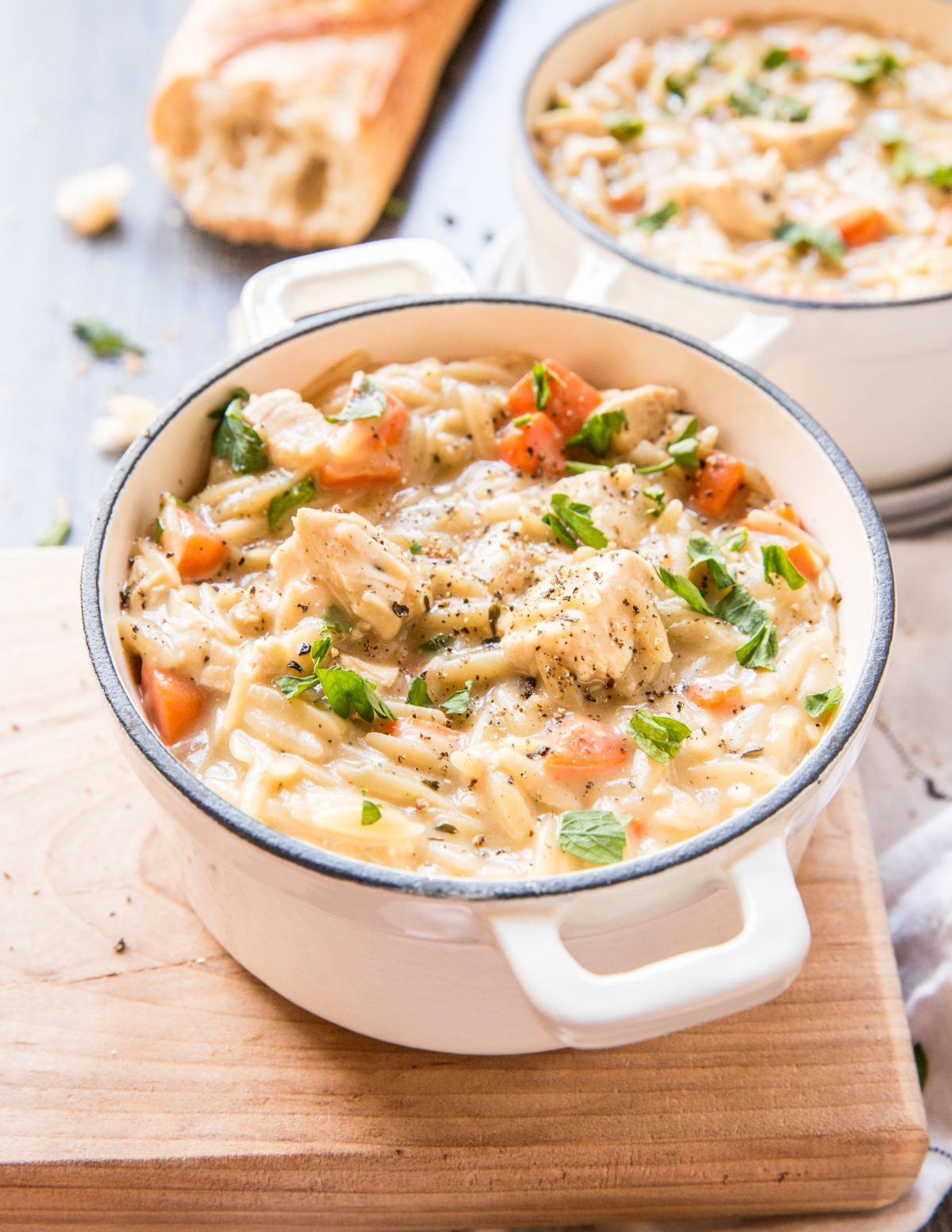 Side shot of a small bowl of chicken soup with orzo and carrots on a wooden cutting board