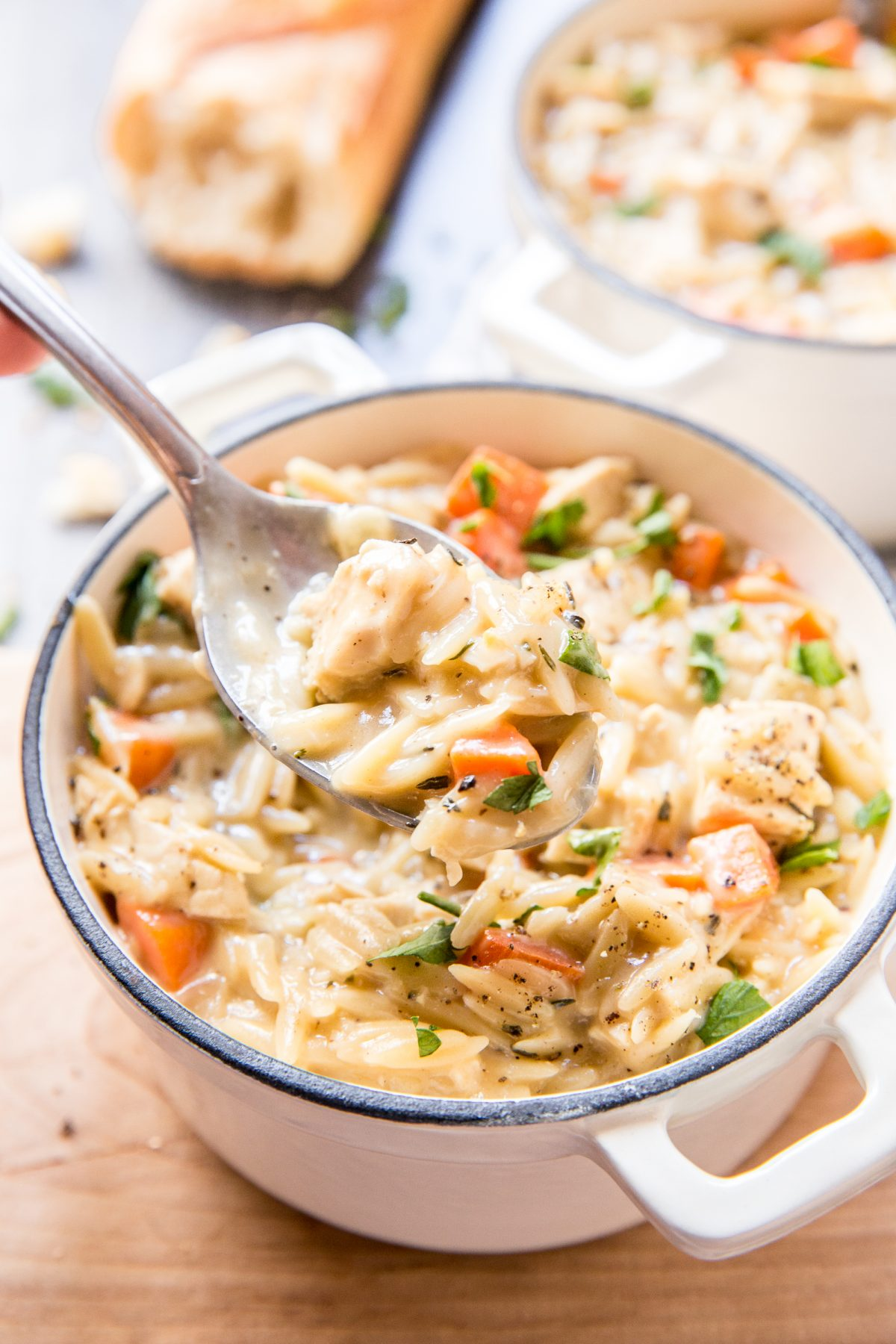 A spoonful of orzo, chicken, and carrots in a white and blue soup bowl