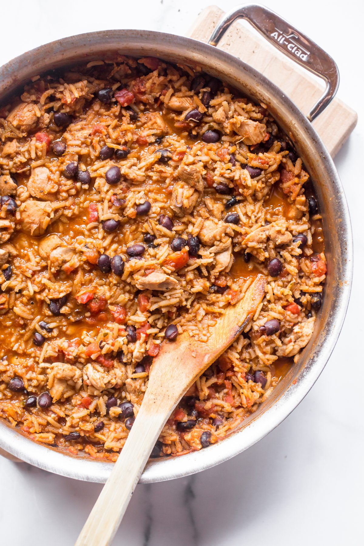 Overhead photo of One Pan Mexican Chicken and Rice. There is a wooden spoon in the pan. There is no cheese covering the chicken and rice in this photo.