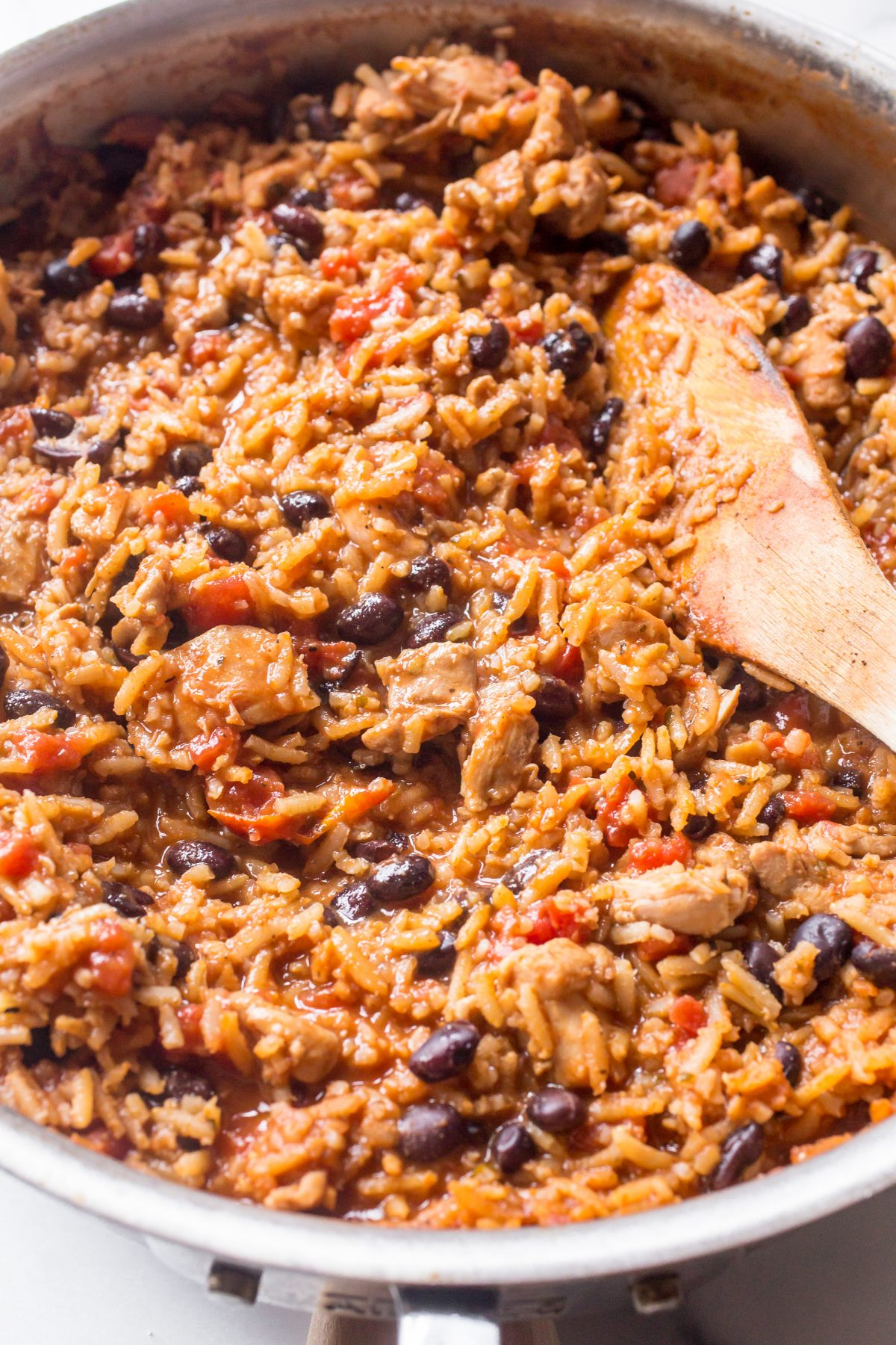 A pan of Mexican chicken, black beans, and rice with a wooden spoon