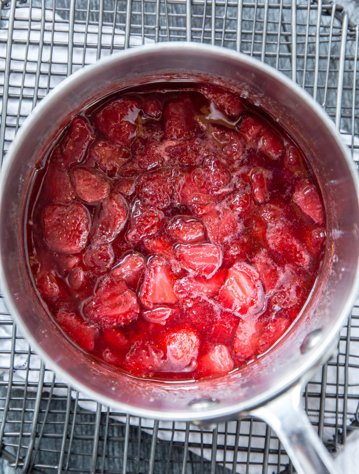 A metal sauce pot filled with strawberry sauce with some strawberry chunks