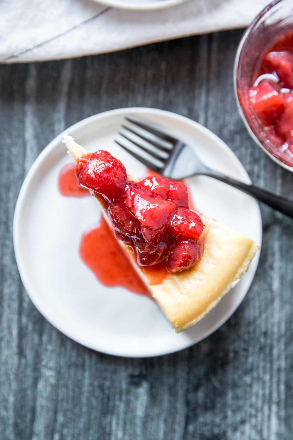 Overhead shot of a slice of cheesecake topped with strawberries and sauce on a white plate
